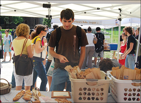 Adrian Rothschild '12 taste-tests a few breads at the Wave Hill Breads of Wilton, Conn. tent.