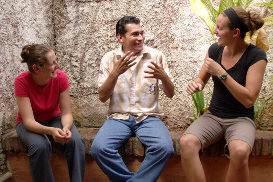 Anna Shusterman, left, and Lisa Drennan '09 speak to a Deaf man by using Nicaraguan Sign Language. The language is only 30 years old.