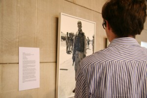 """Will Krieger '11 looks at a photograph from An-My Le's """"29 Palms."""""""