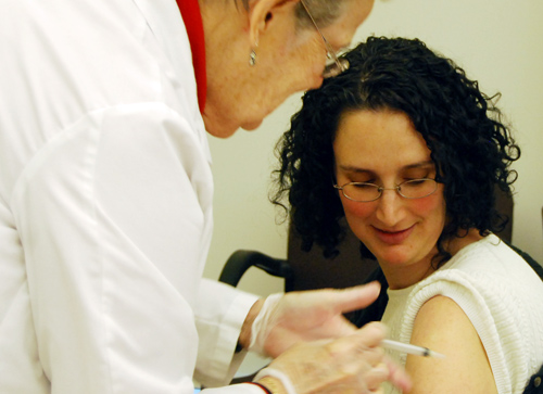 Licensed Practical Nurse Ida Blumberg inoculates Abigail Hornstein, assistant professor of economics. Hornstein didn't mind watching while getting her shot. The vaccine was free to all Wesleyan employees enrolled in the CIGNA health plan.