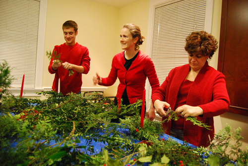 Donning festive red sweaters, XX, Cathy Crimmins Lechowicz and XXX worked side-by-side to create their centerpieces.