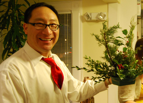 Frank Kuan, director of community relations and secretary of the university, created a centerpiece using evergreen branches and holly. All tools, greens and containers were supplied.