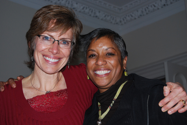 Joan Adams, assistant to the president, shares a holiday hug with and Sonia BasSheva Mañjon, vice president for diversity and strategic partnerships.