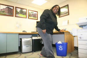 Dawn Brown, area coordinator in Residential Life, tosses office waste into her recycle bin.
