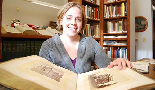 Valerie Gillispie, assistant university archivist at Wesleyan University, flips through the pages of a class photo album dated 1873. A gentleman from Newark, Del. found the album in a pile of books and donated it back to Wesleyan this month. (Photo by Olivia Bartlett)
