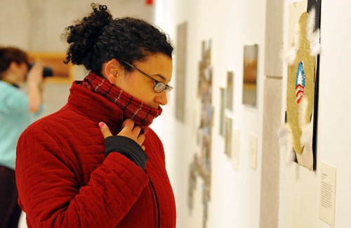 Carolyn Ariori '09 looks over artwork during the show's grand opening.