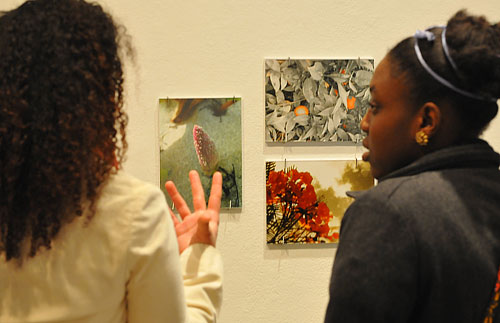 """MelanieNelson '09, at left, talks about her photographs titled """"Naturaleza Interior"""" to Marsha Jean-Charles '11."""