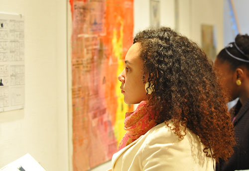 Melanie Nelson '09, also an artist in the show, looks at her peers' artwork.