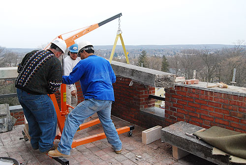 Contractors use a davit to hoise a limestone coping cap on the fourth-floor terrace. The fourth floor will house The Shapiro Creative Writing Center and a Certificate Program in Creative Writing. A meeting room will overlook the terrace.