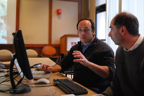 At left, Emmanuel Paris-Bouvret, director of the Language Resource Center and coordinator of Less Commonly Taught Languages, teaches James McGuire, professor of government and Latin American studies, about Google video applications.