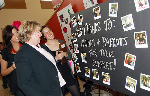 "University Relations held a ""Tuition Transition"" celebration March 27 in Usdan University Center to thank alumni and parent donors for their financial support. Pictured, from left, Sarah Bell '09, Pam Vasiliou, director of the Wesleyan Fund, and Katie Borfshever '09 look over a poster on display."