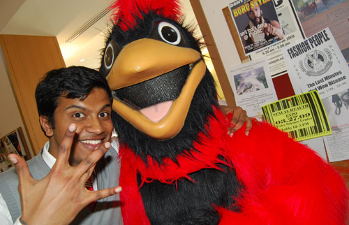 """Anand Satchidanandan, assistant director of The Wesleyan Fund, gestures a Wesleyan """"W"""" with the cardinal during the event. Students were handed informational cards, cookies and fortune cookies. (Photos by Olivia Bartlett)"""