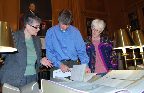 "At left, Suzy Taraba, university archivist and head of Special Collections, speaks to Phil Resor, assistant professor of earth and enviornmental sciences, and Suzanne O'Connell, chair and professor of earth and environmental sciences, director of the Service Learning Center, during the Special Collections and Archives Earth Day Open House April 22. Taraba is explaining printer and publisher Robin Price's ""43."" Paper maps from locations along the 43rd parallels are bound in an accordion that structurally supports the main text, which is printed on graph paper and joined together as an accordion."