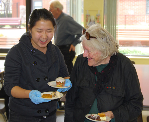 Jenny Lo '10 speaks with a senior citizen at the International Dessert Buffet.
