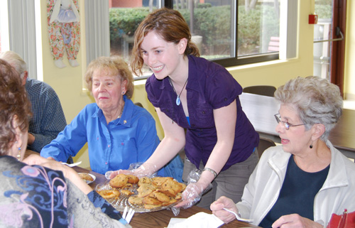 Leslie Pyne '12 offers a table of senior citizens cookes and muffins.