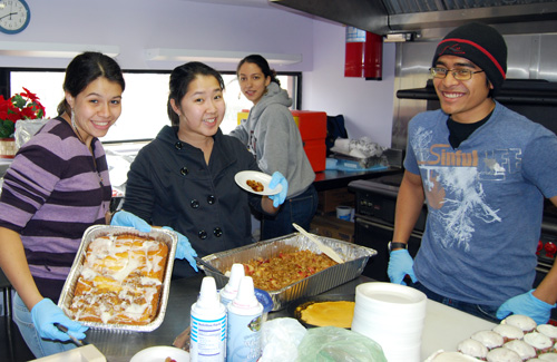 From left, Melina Aguilar '10, Jenny Lo '10, Joyous Bey and Sandy Yudhistira '12 prepare dessert plates inside the Senior Center's kitchen. Under the direction of Wesleyan's Center for Community Partnerships, the students baked or cooked their own desserts, or asked area eateries to donate desserts for the event.