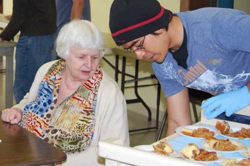Sandy Yudhistira '12 serves a local senior citizen a tasty treat at the annual International Dessert Fair April 2 at the Senior Center in Middletown.