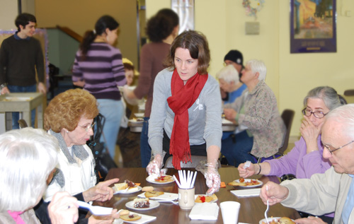 Cathy Crimmins Lechowicz, director of community service and volunteerism, serves a group of seniors, while students in the background, prepare the plates.