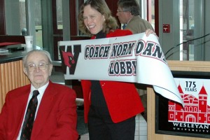 "Barbara-Jan Wilson, vice president for University Relations, holds up a banner declaring the space ""Coach Norm Daniels Lobby"" during Daniels's 100th birthday celebration."