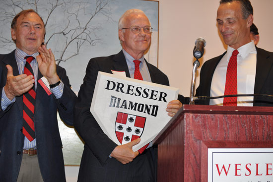 "Wesleyan President Michael Roth, right, presented Chair of the Board of Trustees Jim Dresser '63 with a homeplate during a ceremony May 21 in Daniel Family Commons, commemorating the dedication of  Wesleyan's baseball field as ""Dresser Diamond."" Pictured at left is former Wesleyan President Doug Bennet."