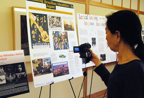 Eiko Otake, visiting instructor in dance, photographs a student's poster.
