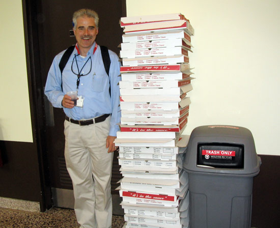Bill Nelligan, director of environmental halth, safety and sustainability, stands by empty pizza boxes from the party. Nelligan taught the fellows about safety issues. (Photos by Laurel Appel)