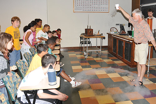 Brian Stewart, associate professor pf physics, demonstrates how liquid nitrogen looks like water but evaporates rapidly at room temperature. Fifth grade students from Snow Elementary School toured the Wesleyan sciences June 19.