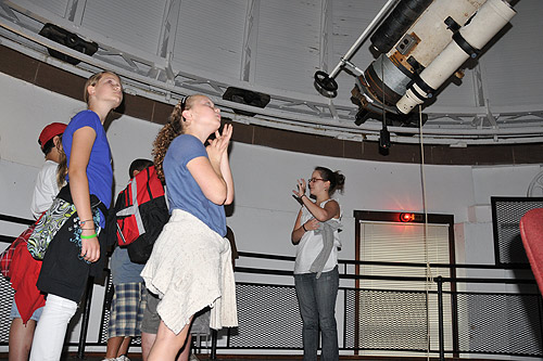 Astronomy graduate student Amy Langford, at right, teaches the students about Wesleyan's Alvan Clark 20-inch refractor telescope inside the observatory. (Photos by Olivia Bartlett)