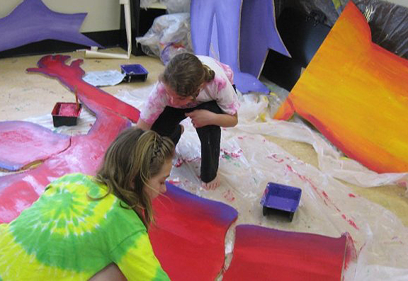 Children work on sections of the mural inside the GSAC.