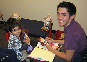 Christian Hoyos '11 works with a 3-year-old during an experiment on sharing behavior during a summer internship at the Social Cognitive Development Lab at Yale University.