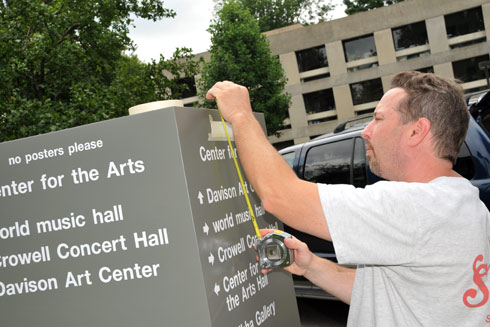 Paul Berneche of Agnoli Signs in Springfield, Mass. lays the new lettering on the CFA sign Aug. 12.