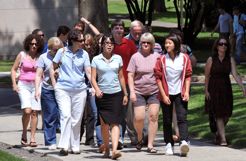 XX, center in blue shirt, leads a tour down College Row. All events begin at the Stewart M. Reid House. No pre-registration is necessary for campus tours or group information sessions.