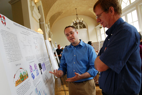 """Chemistry graduate student Daniel Czyzyk, center, explains his research titled """"Heptosyltransferase I and its Role in Biofilm Formation."""" Czyzyk's advisor is Erika Taylor, assistant professor of chemistry."""