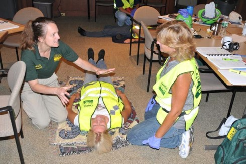 "Holly Jacobs from the Manchester Community Emergency Response Team (CERT) left, teaches Joyce Topshe, associate vice president for facilities, at right, how to properly give a ""head-to-toe assessment"" on an accident victim. Stacy Baldwin, construction project coordinator, plays the role of an injured person."