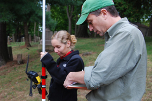 "John Hinchman, a lecturer and research specialist in the Architectural Conservation Laboratory of the Historic Preservation Program at the University of Pennsylvania, teaches Anne Calder '11 how to conduct a digital site survey using a total station. The equipment records the 3-D location of the corner of each stone on the site, and results in an accurate representation of the cemetery. Calder is enrolled in the class, ""The Study of Material Culture: Marking the Past in Middletown."""