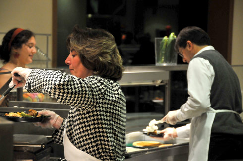 Pictured in center, Valerie Marinelli, administrative assistant in the Environmental Studies Program and McNair Program, serves dinner.