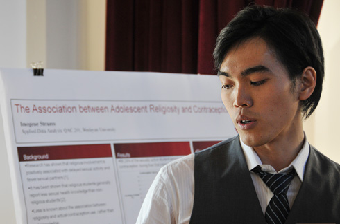 "I-Hui Chow '12 explains his research titled ""Is adolescent smoking associated with lust and romantic commitment?"" during the Quantitative Analysis Center's Poster Session Dec. 17 in Beckham Hall. More than 70 students presented posters at the event.  All students are enrolled in the course QAC 201, Applied Data Analysis."