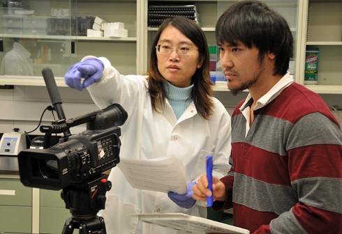 Molecular biology and biochemistry graduate student Jie Zhai explains a scene for videographer Kai-Jie Wang Dec. 15 inside the Hingorani Laboratory. Wang works for the Journal of Visualized Experiments, a peer reviewed, indexed journal devoted to the publication of biological research in a video format. He is filming a project at Wesleyan titled Application of Stopped-flow Kinetics Methods to Investigate the Mechanism of Action of a DNA Repair Protein. 