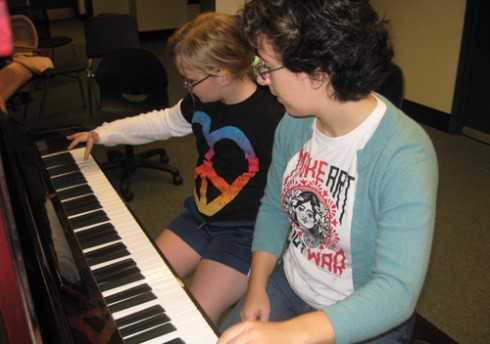 Emily Troll '10 and a GSAC AfterSchool student play piano together.