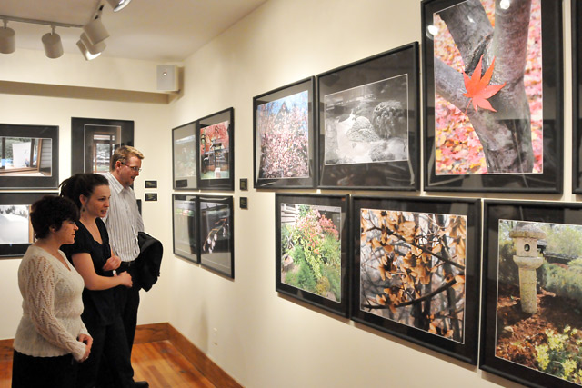 From left, Lisa Calhoun, administrative assistant in the East Asian Studies Program; Brandi Cahill, assistant director of university events and scheduling; and Patrick Dougherty, development researcher/writer; admire photos in the exhibit. Curator Dowdey included images of the garden captured in every season.