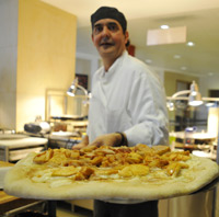 """The Pizza Man"" Mert Champagne shows off a cream cheese and apple pizza, fresh from the oven."