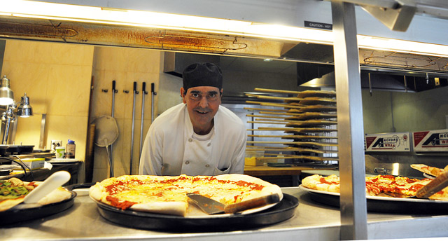 Mert Champagne, a cook in Usdan University Center's Marketplace, takes special requests at the pizza station. His specialty is a white pizza made with garlic, ricotta cheese, plum tomatoes, mozzarella and basil. (Photos by Olivia Bartlett Drake)