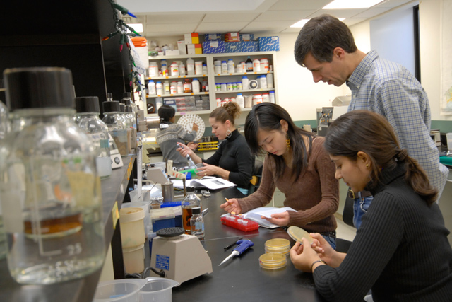 At right, Scott Holmes, associate professor of molecular biology and biochemistry, received a three-year grant to support his research gene expression. His lab uses a budding yeast for the studies. (Photo by Bill Burkhart)