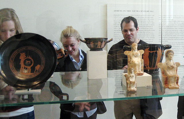 Visiting international student Anna Huber and Jorge Bravo, visiting assistant professor of classical studies, look at a display case of red-figure vases and small votive figurines from classical Athens.