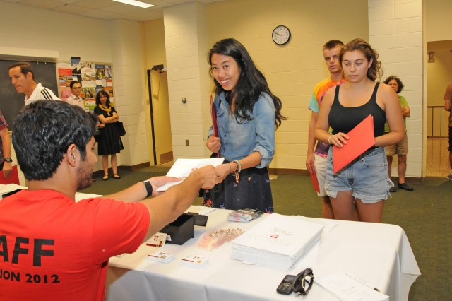 "Claudia Von Nostitz '16 picks up her WesCard on Student Arrival Day from student worker Ali Shajrawi '15. ""I'm betraying my class by saying this but you have an awesome class. 2016 might be the best class on campus,"" Shajrawi says."