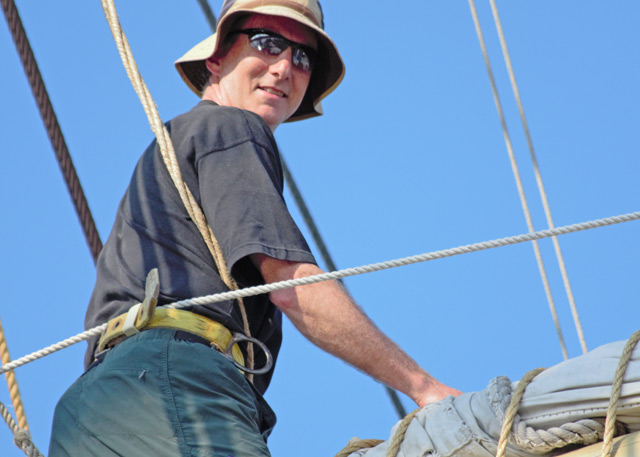 "William ""Vijay"" Pinch, professor of history, adjusts the topsail of the Joseph Conrad, during an NEH-funded summertime institute in June. Pinch participated in the five-week institute, in part, to refine and improve his maritime world history course. (Photo by Heather Agostini)"