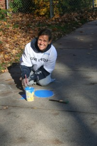 Tracy Mehr-Muska, University Protestant Chaplain, paints a paw at the school.
