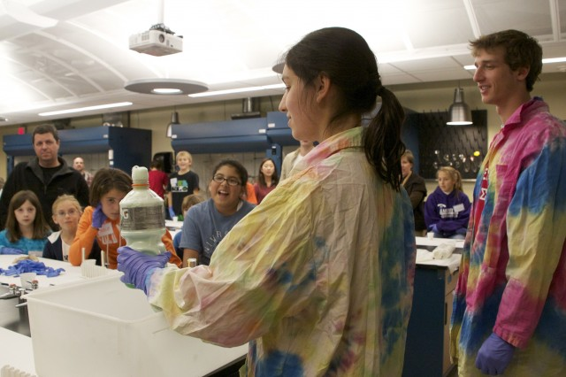 """Rachel Olfson '14 and Bennett Sluis '14 make """"Elephant's toothpaste"""" for Science Day goers."""