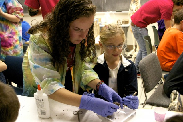 Emily Berman '13 helps Science Day goer Alyssa dissect her owl pellet. The semi-annual afternoon of science activities are designed for the whole family.