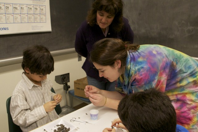 Wesleyan students enrolled in the outreach course taught science lessons and offered hands-on demonstrations. Pictured is Eliza Forman '13 aiding in another careful owl pellet dissection.